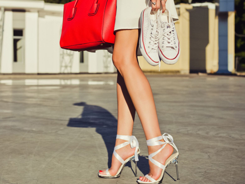 lady wearing high heels holding a pair of sneakers and a red bag